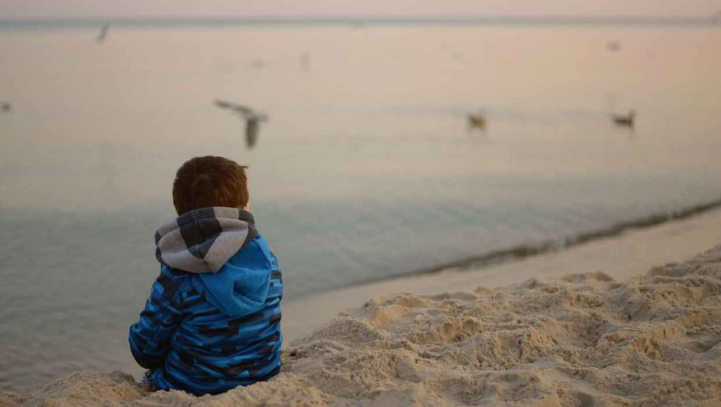 a child on the beach alone